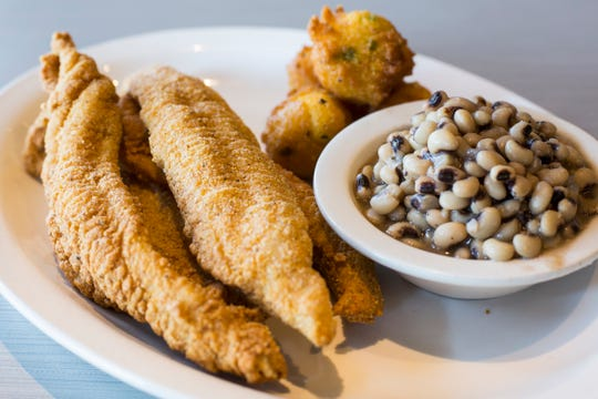 A plate of fried catfish with a side of hushpuppies and black eyed peas at Soul Fish Cafe.