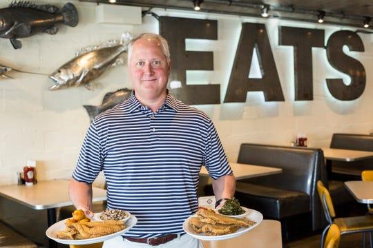 August 28 2018 - Raymond Williams, owner of Soul Fish Restaurant, holds plates of catfish inside of the Soul Fish Restaurant on Poplar Avenue.