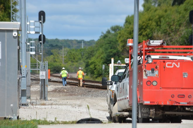 A Canadian National Railway crew inspects a switch and walks down the track after fixing a crossing gate problem at East Moreland Boulevard near Frame Park on Aug. 29. The busy railroad crossing in Waukesha malfunctioned, creating a traffic jam shortly after noon. Traffic was again flowing smoothly by 1:30 p.m.