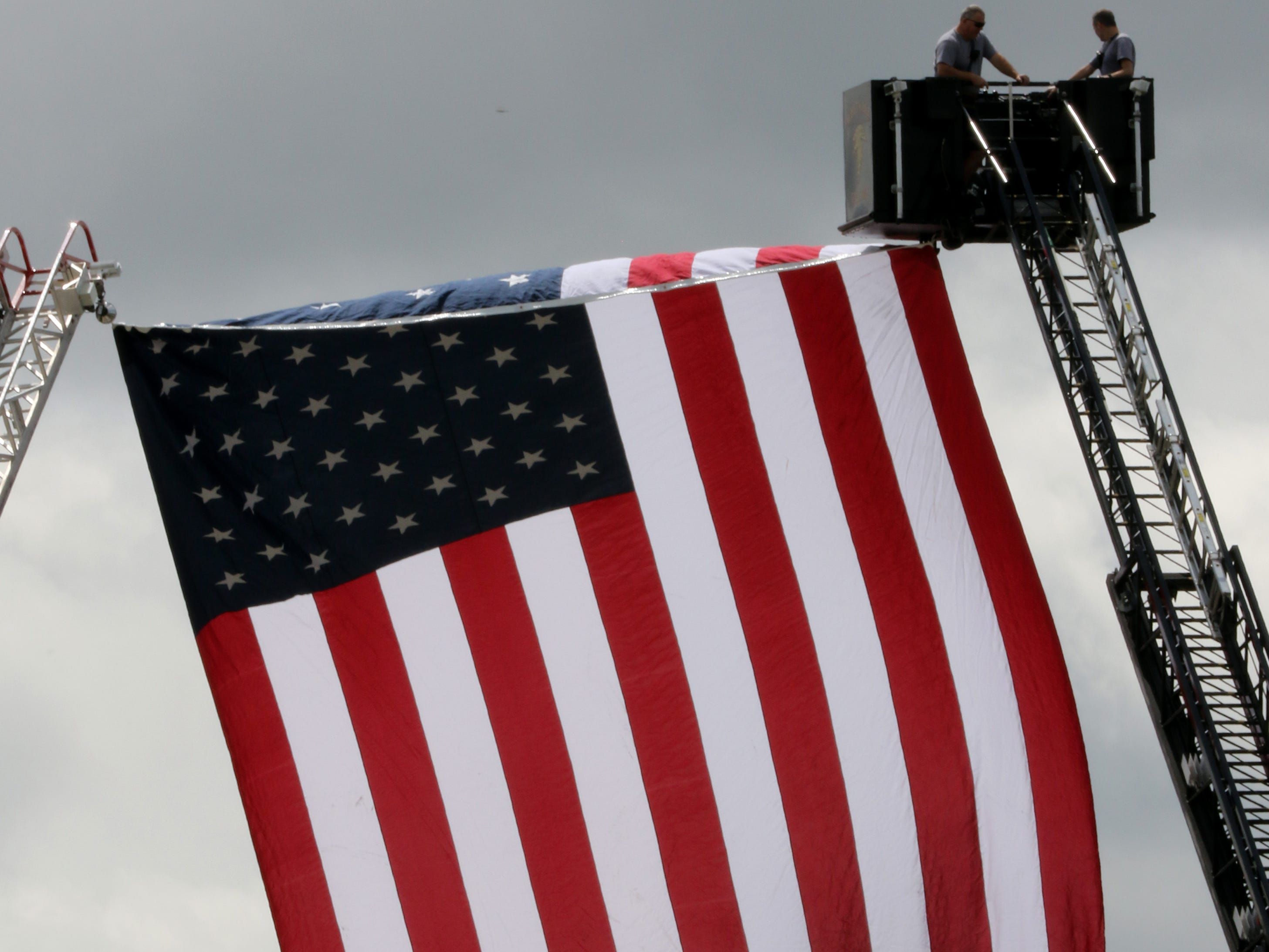 An American flag hangs between two fire ladders over 60th Street on Wednesday for a charity ride benefiting the Wisconsin Veterans Network from House of Harley-Davidson though southern Milwaukee County communities and ending at Veterans Park on the Milwaukee lakefront.