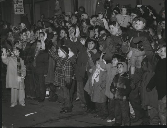Kids wave to Santa Claus as he rides by Santa Clause Saturday night as he rode in Schuster's annual Christmas parade in downtown Milwaukee on Nov. 19, 1955. This photo was published in the Nov. 20, 1955, Milwaukee Journal.