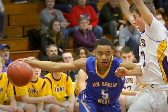 C.T. Kruger/Now Media Group New Berlin West's Desmond Polk drives under New Berlin Eisenhower's Bryce Miller at Eisenhower on Jan. 13. New Berlin West's Desmond Polk drives under New Berlin Eisenhower's Bryce Miller at Eisenhower on Jan. 13.