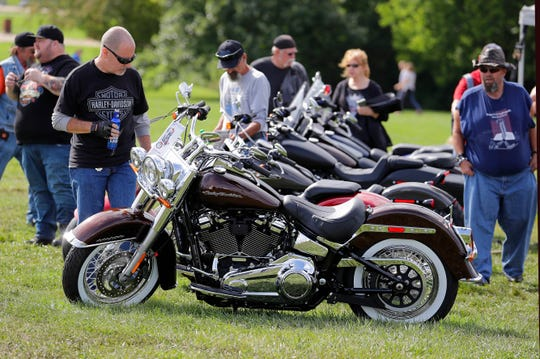 Harley riders check out a new Harley-Davidson Deluxe model on display as thousands pour into Milwaukee for the 115th Anniversary Kickoff Celebration at Veterans Park at the lakefront.