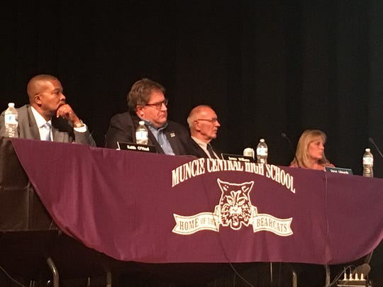 Muncie School Board members Keith O'Neal and Jim Williams, along with emergency manager Steve Edwards and secretary Cheryl Hirst listen to a board member across the stage at Central High School's auditorium on Tuesday night.