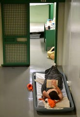 An inmate reads a book in the Wilson County jail where overcrowded conditions force some inmates to sleep on mattresses on the floor. Monday Aug. 27, 2018, in Nashville, Tenn.