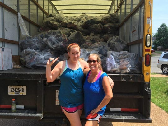Sarah Jones and her mother Kim Lynch pose in front of 6,050 pairs of gently worn shoes, which raised over $2,000 toward the family's adoption process.