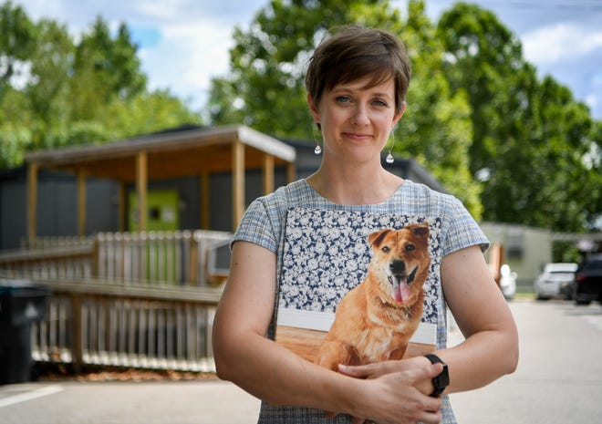 Natalie Corwin, CEO of Pet Community Center, holds a portrait of her late dog Sophie, who inspired her to open the center, on Aug. 29, 2018. The center now does more than 7,000 free or discounted spay and neuter surgeries each year.