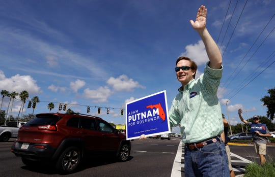 Florida Republican gubernatorial candidate Adam Putnam waves at motorists as he campaigns Tuesday, Aug. 28, 2018, in Brandon, Florida.