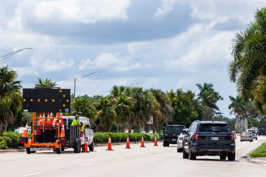 Landscape workers collect traffic cones after completing their work on the median along Livingston Road in North Naples on Wednesday, August 29, 2018. Workers placed warning signs throughout the street and blocked the left lane for both north and southbound traffic as they worked. A landscape worker died on Monday morning after he was struck by a semitrailer as he was working in a landscaped median.