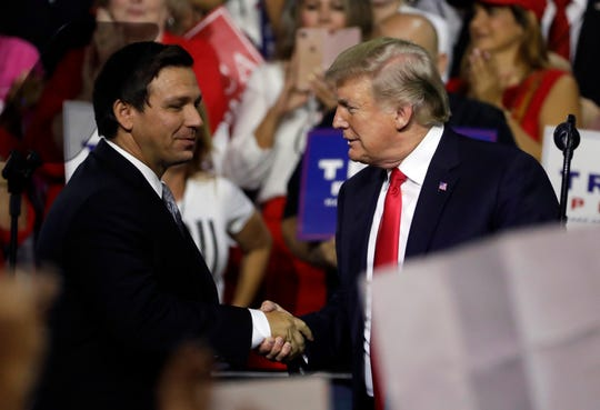 President Donald Trump, right, shakes hands with Florida Republican gubernatorial candidate Ron DeSantis during a rally Tuesday, July 31, 2018, in Tampa.
