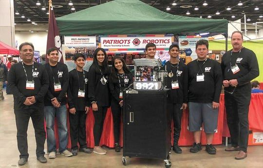 Wayne Hills technology teacher Robert Yost (right) stands with his high-scoring robotics team.