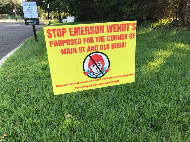 Signs protesting a proposed Wendy's in Emerson are lined along Westwood's side of Old Hook Road.