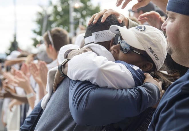 NY Giants cornerback Grant Haley, left, hugs his mother, Dr. Carla Neal-Haley, right, after a game last season at Penn State. Haley is inspired by Mom's fight against liver disease as she waits for an implant.