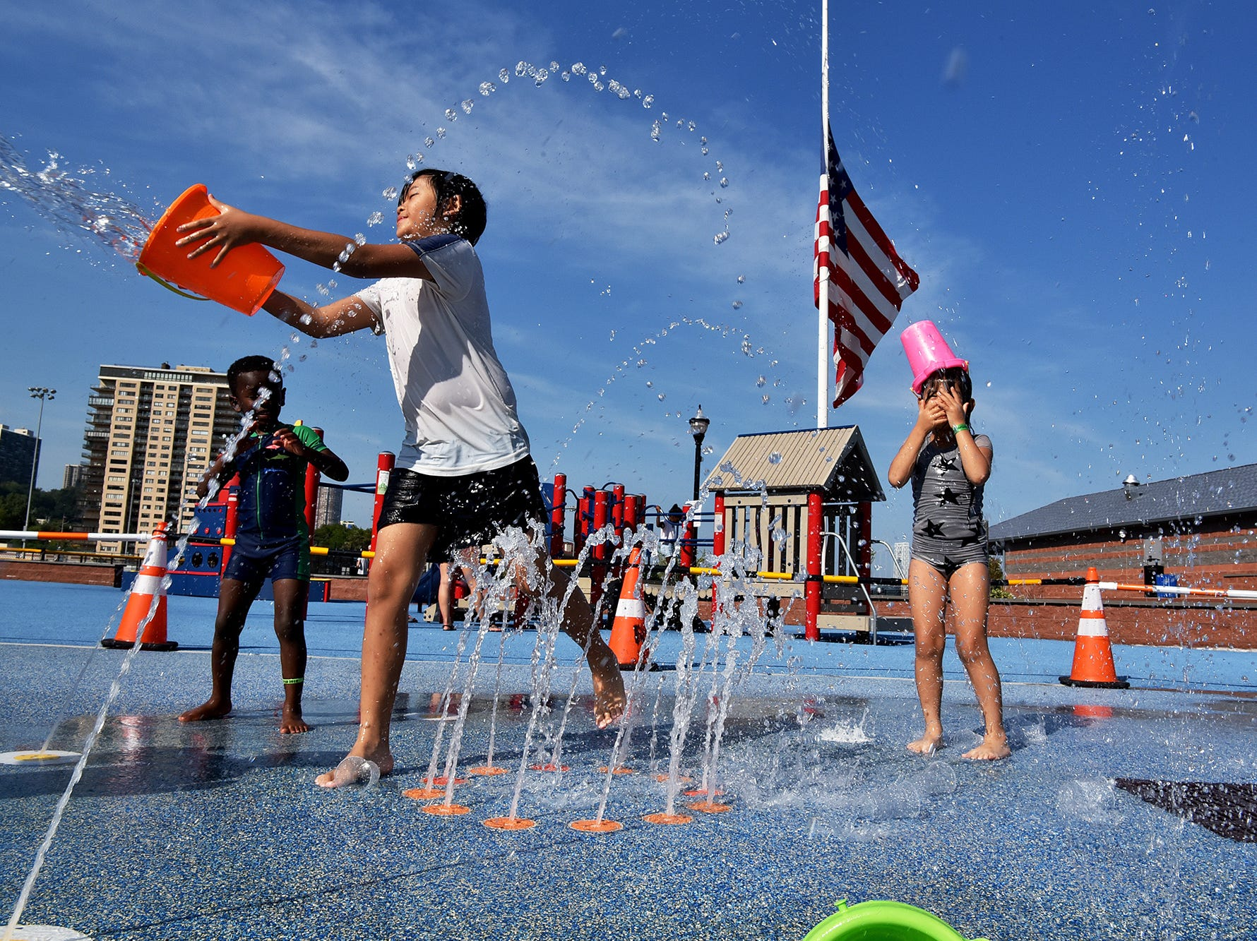 Children play at the sprinklers at Veterans Memorial field in Edgewater, NJ.