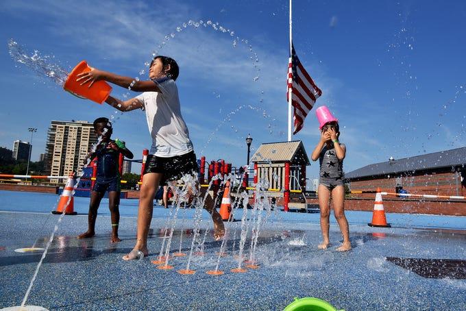 Children play at the sprinklers at Veterans Memorial field in Edgewater, NJ.