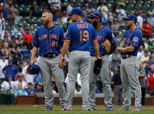 New York Mets infielders Todd Frazier (21), Jay Bruce (19), Amed Rosario (1) and Jeff Mcneil (68) watch relief pitcher Daniel Zamora during the 11th inning of a baseball game against the Chicago Cubs, Wednesday, Aug. 29, 2018, in Chicago. The Cubs won 2-1 in 11 innings. This game had been suspended in a 1-1 tie in the 10th inning due to severe weather conditions the night before.