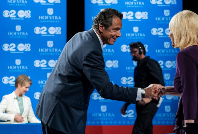 New York Gov. Andrew Cuomo shakes hands with a moderator as opponent Democratic New York gubernatorial candidate Cynthia Nixon prepares before a gubernatorial debate at Hofstra University in Hempstead, N.Y., Wednesday, Aug. 29, 2018. (AP Photo/Craig Ruttle, Pool)