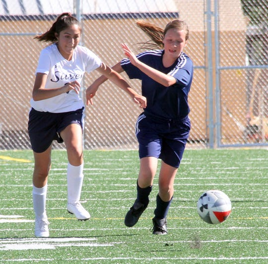 Eighth-grade varsity Lady 'Cat Santana Valentine (right) chases down a free ball during Deming's 1-0 victory over visiting Silver High on Tuesday.