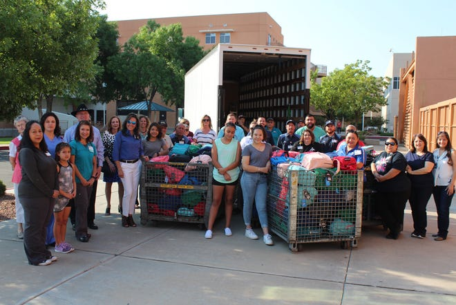 Memorial Medical Center employees and their families pose with staff from Las Cruces Public Schools and the nearly 400 backpacks filled with school supplies MMC donated on Thursday, Aug. 2 at the hospital.