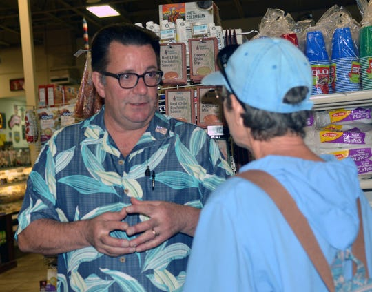 Toucan Market co-owner Bob Baur takes time to chat with a customer on August 29, 2018.