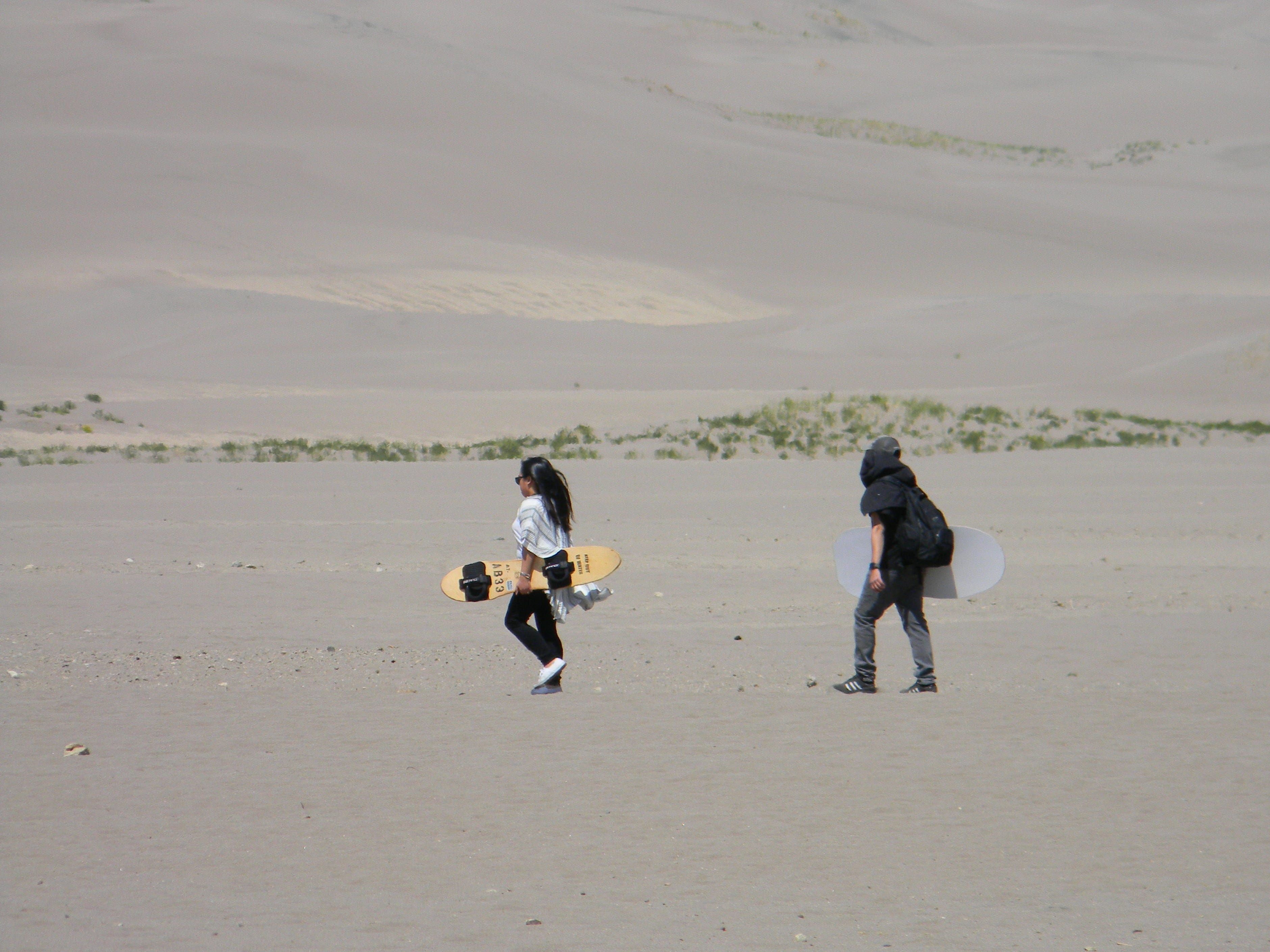 Youth carry sand sled and sand board, wondering perhaps if the sand behaves like snow … or if they face new and interesting challenges at Great Sands Dunes National Park.