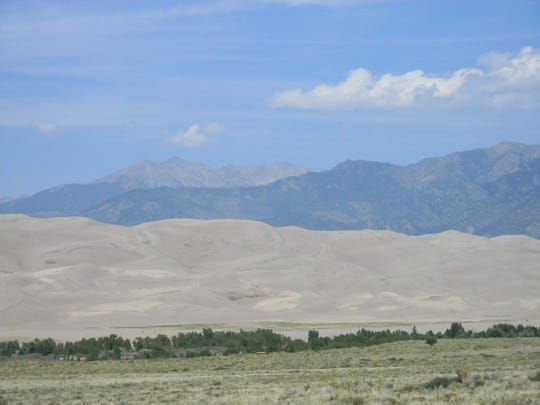 Mount Humboldt, 14,000-feet tall, dominates the Sangre de Cristo mountains that corral the sand creating the great dunes, foreground at Great Sands Dunes National Park.