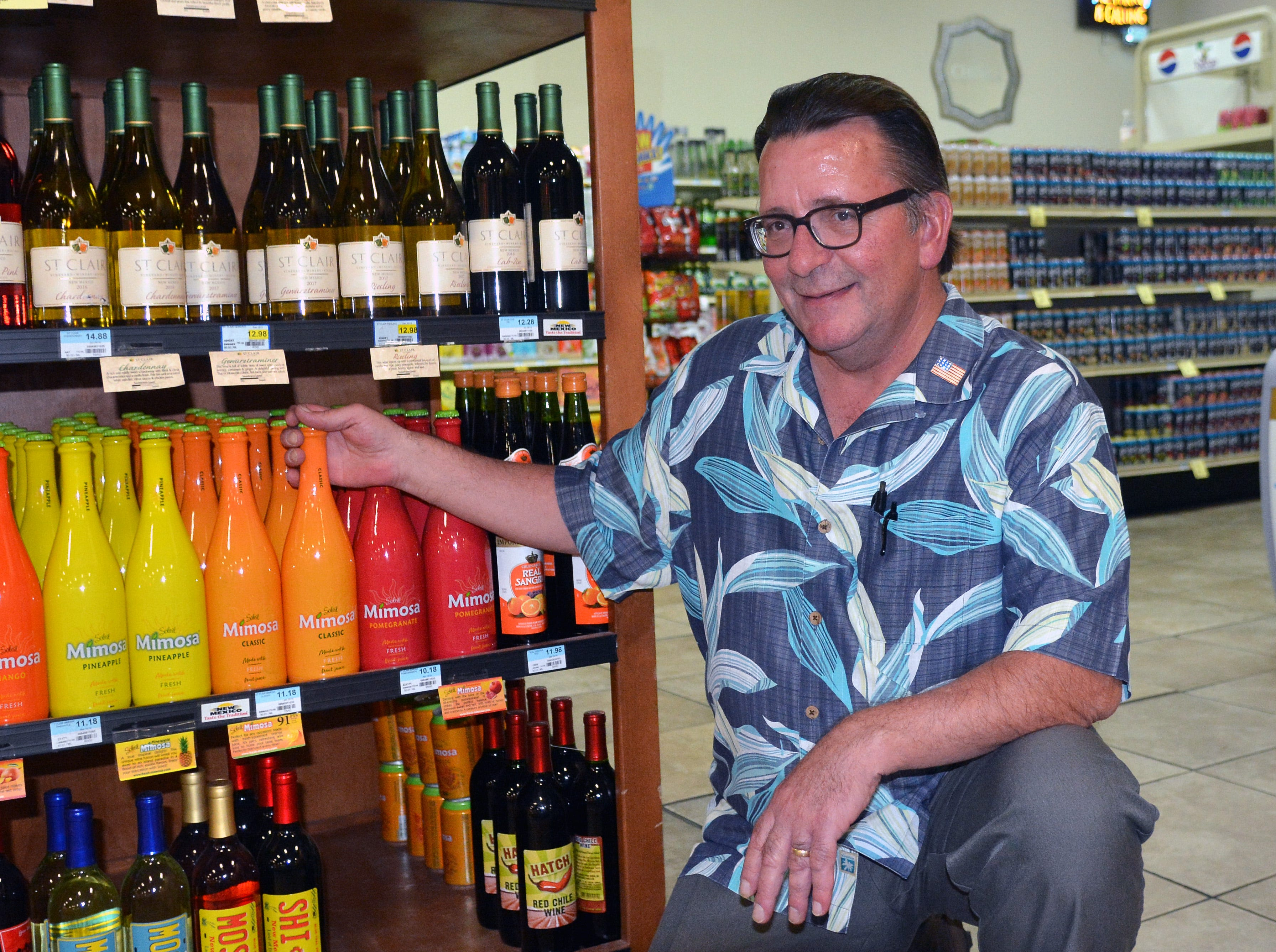 Toucan Market co-owner Bob Baur shows off one of the many locally produced bottles of wine carried at his store on August 29, 2018.