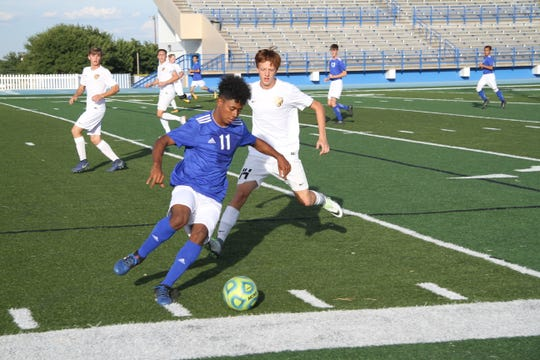 Carlsbad's Denilson Aguilar battles Alamogordo's Bryson Kangas for position early in the first half of Tuesday's match. The Tigers defeated the Cavemen, 2-1.
