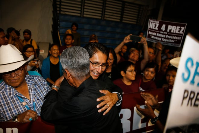 Navajo Nation presidential candidates Jonathan Nez and Joe Shirley Jr. hug Tuesday at the Window Rock Sports Center in Window Rock, Ariz., after finishing first and second, respectively, in the primary election.