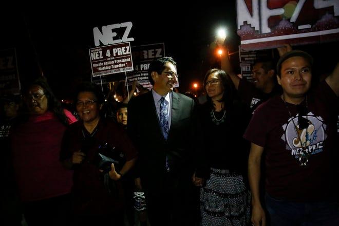 Jonathan Nez and his wife Phefelia Herbert-Nez walk with their supporters to the Window Rock Sports Center Tuesday in Window Rock, Ariz.