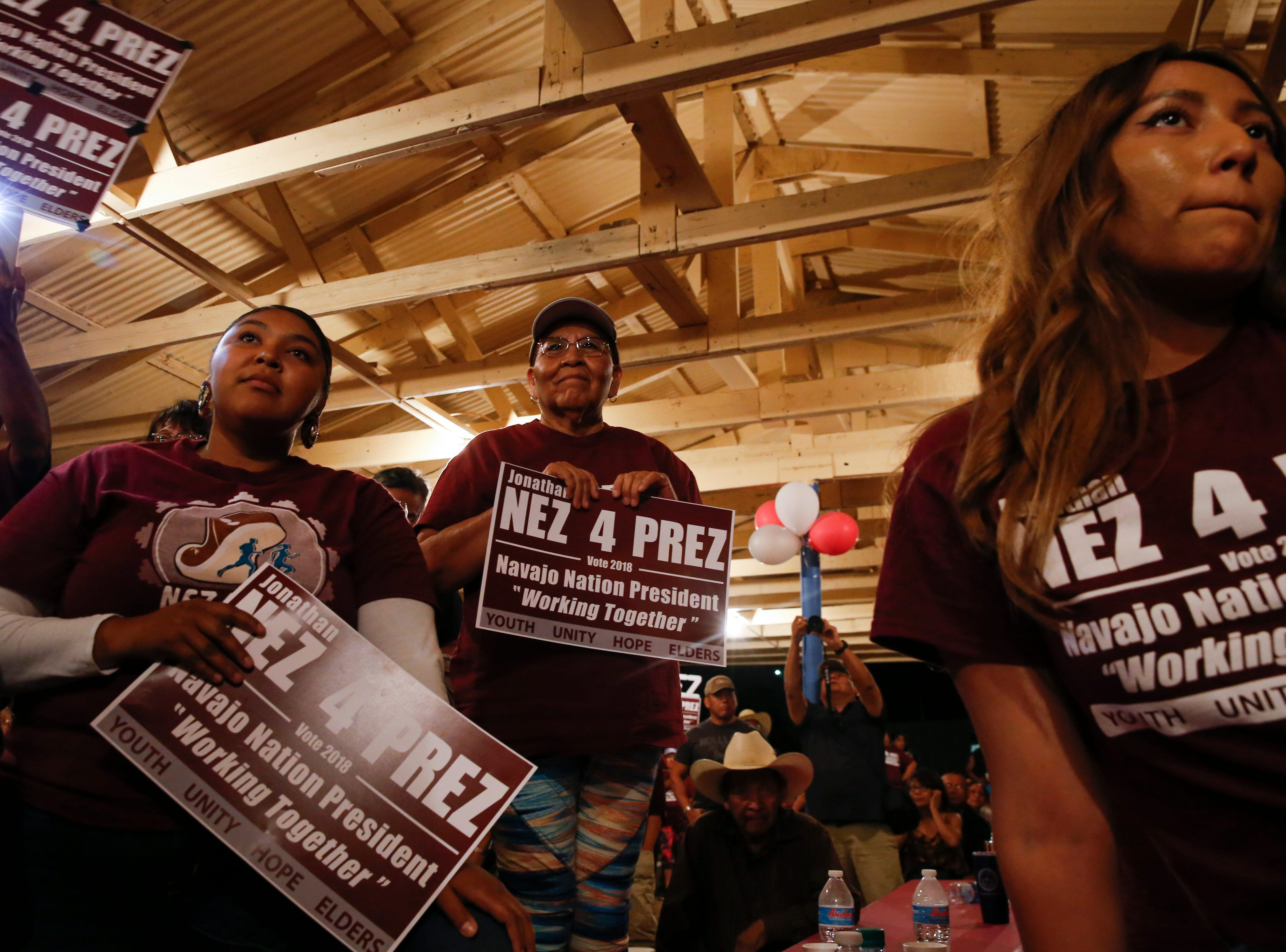 Brittany Tabor, left, listens to a speech by Navajo Nation Presidential candidate Jonathan Nez at his campaign party, Tuesday, Aug. 28, 2018 at the Navajo Nation Fair Grounds in Window Rock, Arizona.
