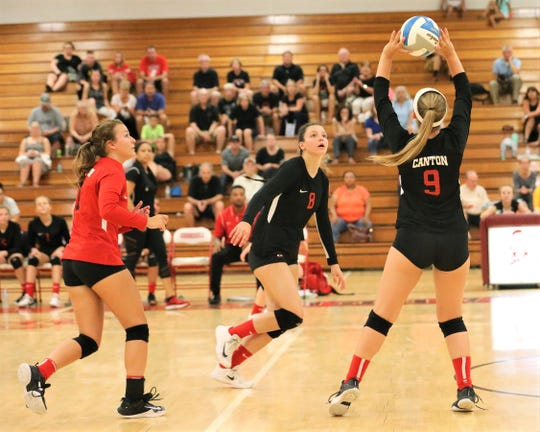 Canton's Amanda Wilyard (9) sets up teammate Holly Stefanek (8) with libero Allie Tanana backing up.