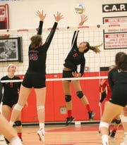 Canton's Miri Hazaar (6) goes high for the tip against Churchill's Summer Clark (15).