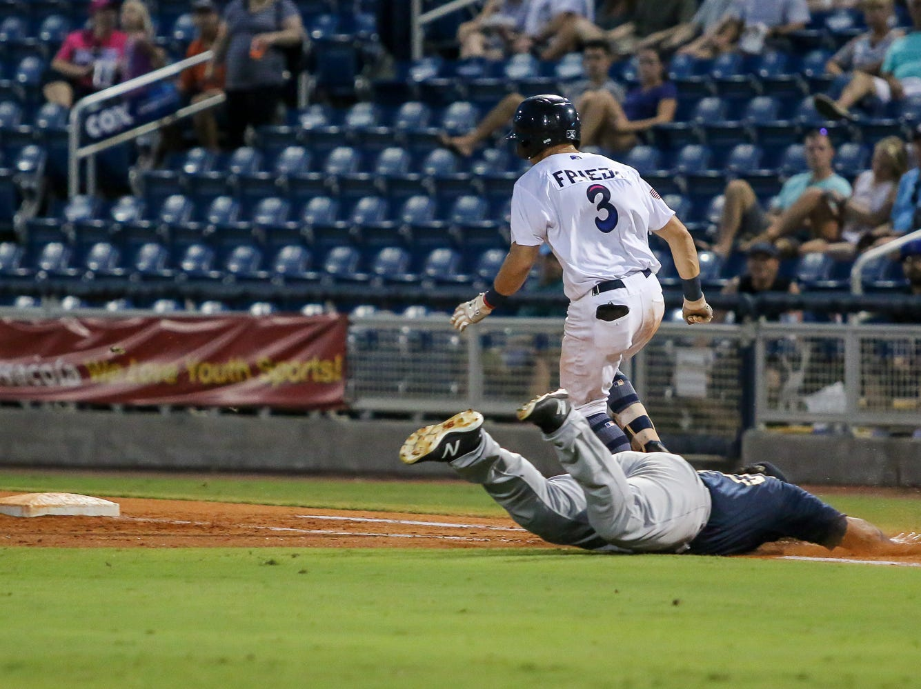 After laying down a bunt, Pensacola's TJ Friedl (3) beats the diving tag by Mobile first baseman Alexis Olmeda (25) during the Blue Wahoos' last home game of the regular season on Tuesday, August 28, 2018.