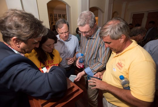 Pensacola Mayorial candidate, Grover Robinson, far right, and a group of his supporters huddle together to monitor the results of the election during a victory party at Robinson home on Tuesday, Aug. 28, 2018.