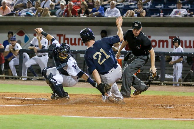 Mobile's Brandon Sandoval (21) beats the tag by Pensacola catcher Chris Oakey (5) to score a run during the Blue Wahoos' last home game of the regular season on Tuesday, August 28, 2018.