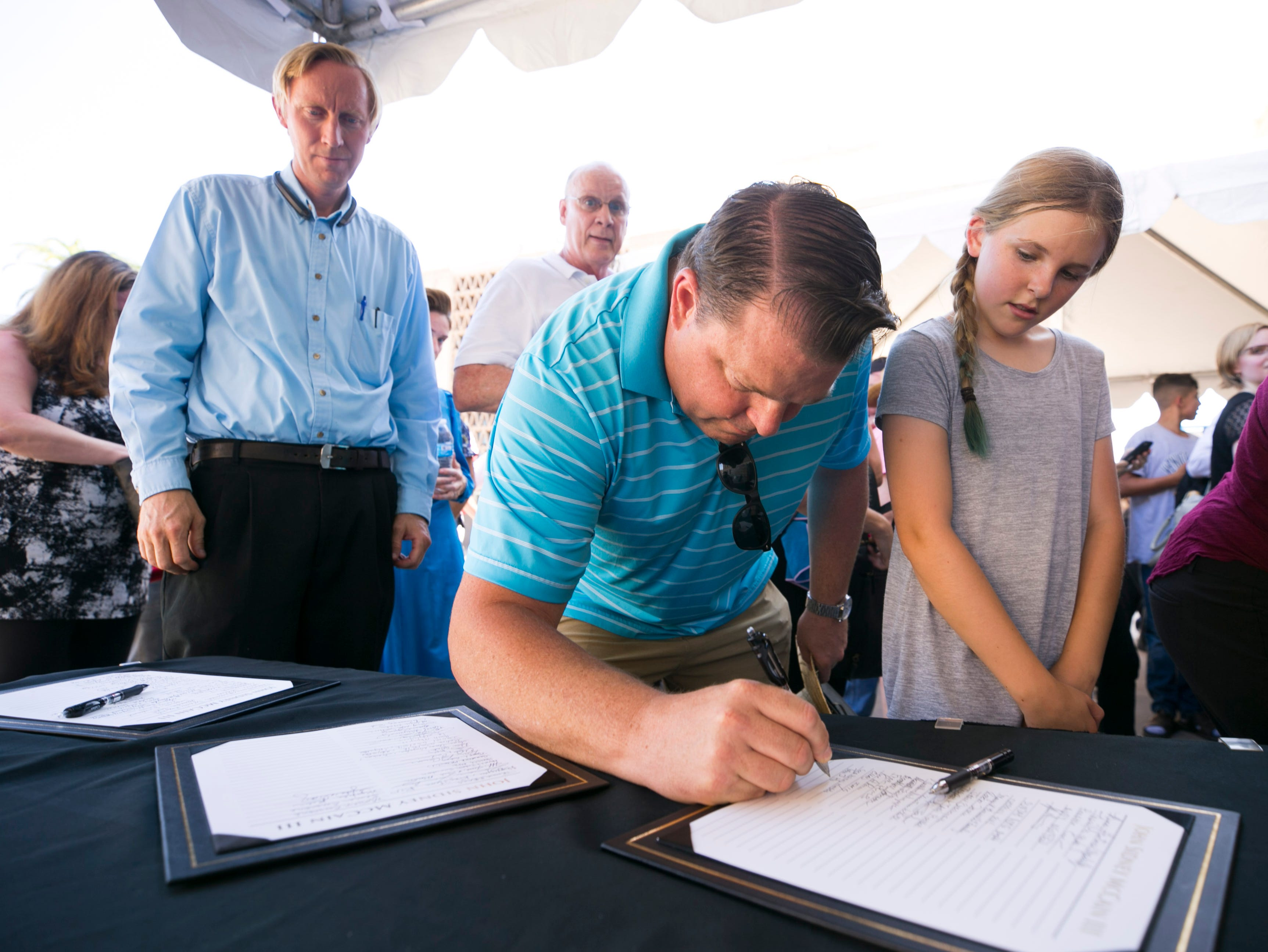 Tobin Holmes of Riverside, California, and his daughter, Cora Holmes, sign a guest book before entering the Arizona state Capitol to pay their respects to Sen. John McCain in Phoenix on Aug. 29, 2018.