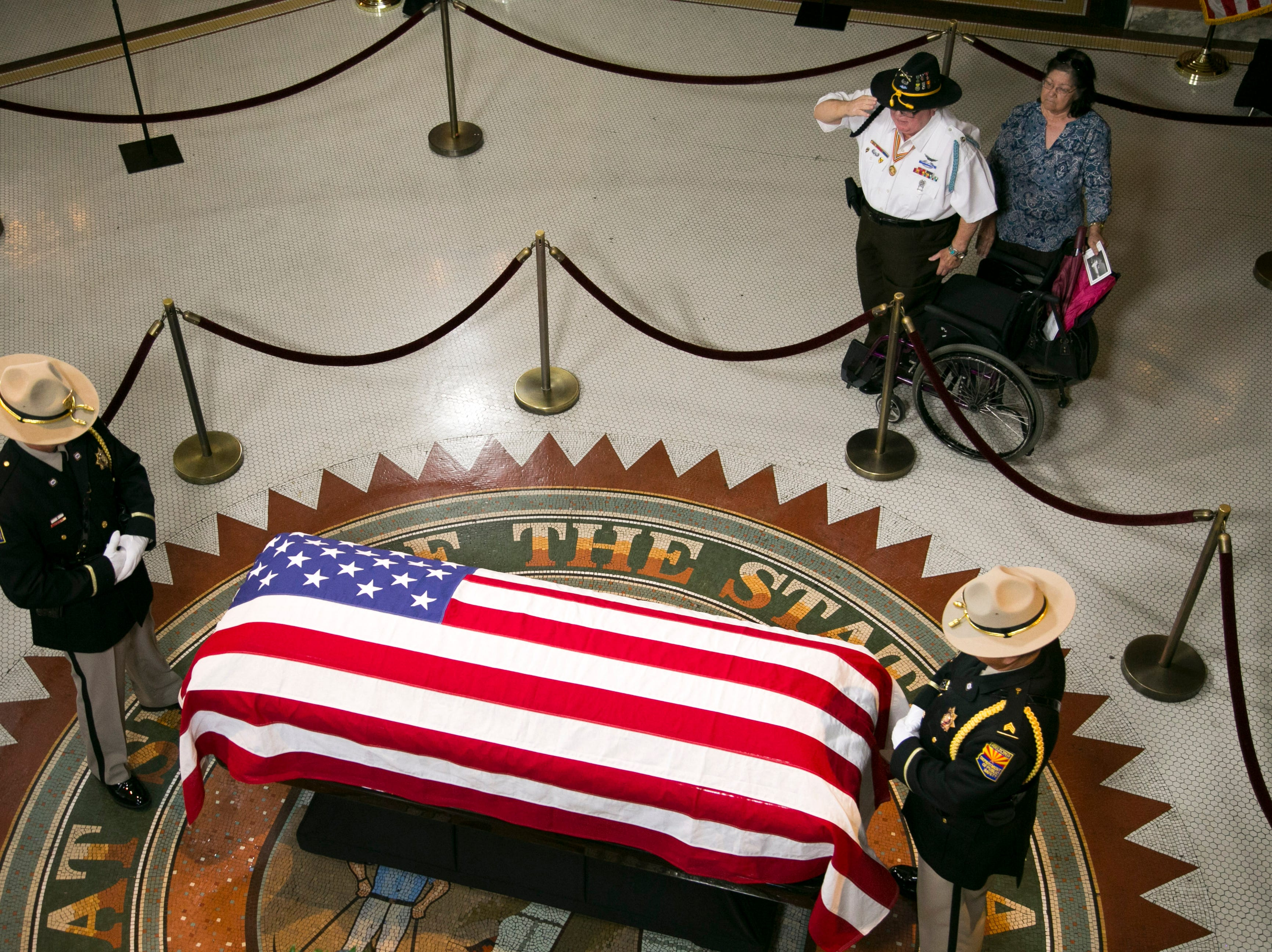 Antonio Chavez of Phoenix, a U.S. Army veteran of the Vietnam War, salutes Sen. John McCain lying in state, as his wife, Maria Chavez, looks on in the state Capitol in Phoenix on Aug. 29, 2018.