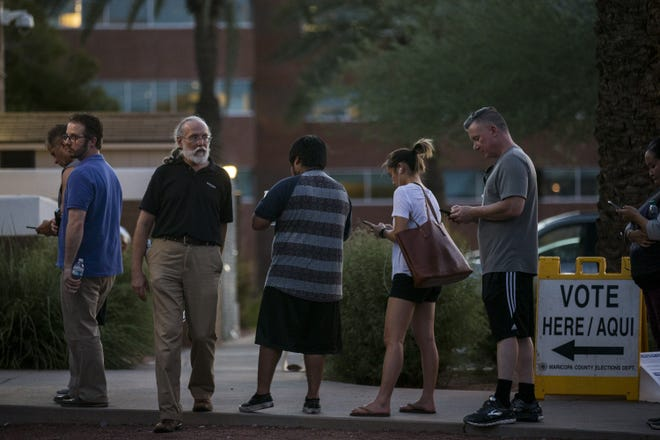 People wait in line to vote on Tuesday, Aug. 28, 2018, at the Phoenix Public Library Century Branch in Phoenix.