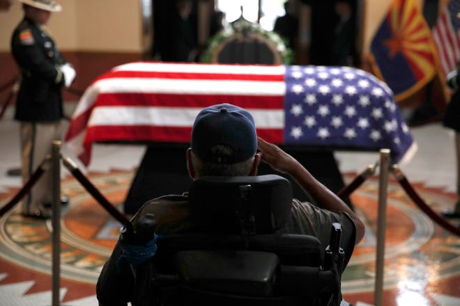 A former serviceman salutes near the casket during a memorial service for Sen. John McCain, R-Ariz., at the Arizona Capitol on Wednesday, Aug. 29, 2018, in Phoenix.