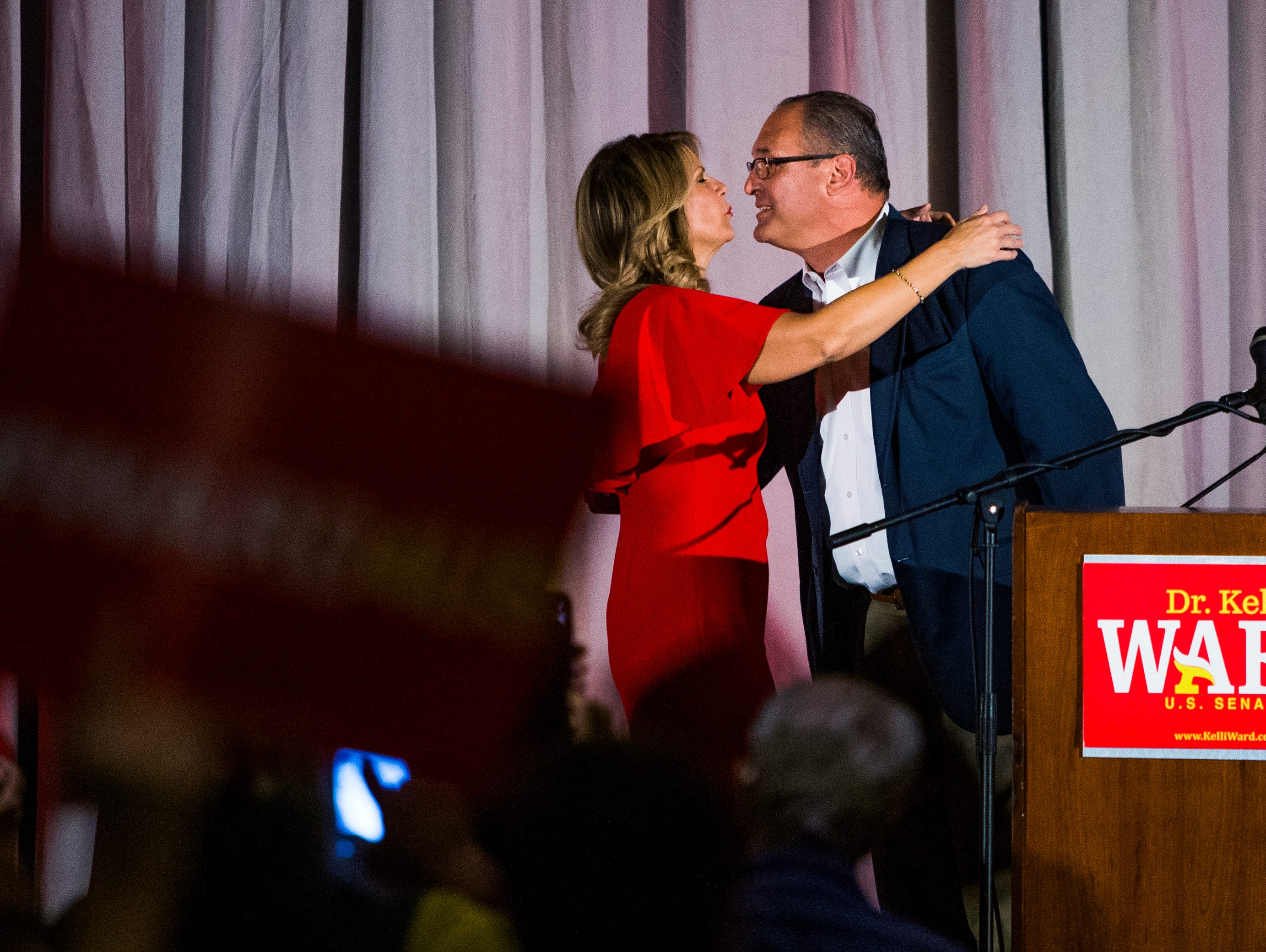 Kelli Ward gets a kiss from her husband, Dr. Michael Ward, before greeting supporters at a primary election night party at Embassy Suites Scottsdale on Aug. 28, 2018.