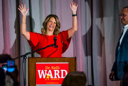 Kelli Ward greets the crowd as her husband, Dr. Michael Ward (right), watches during a primary election night party at Embassy Suites Scottsdale, Aug. 28, 2018.