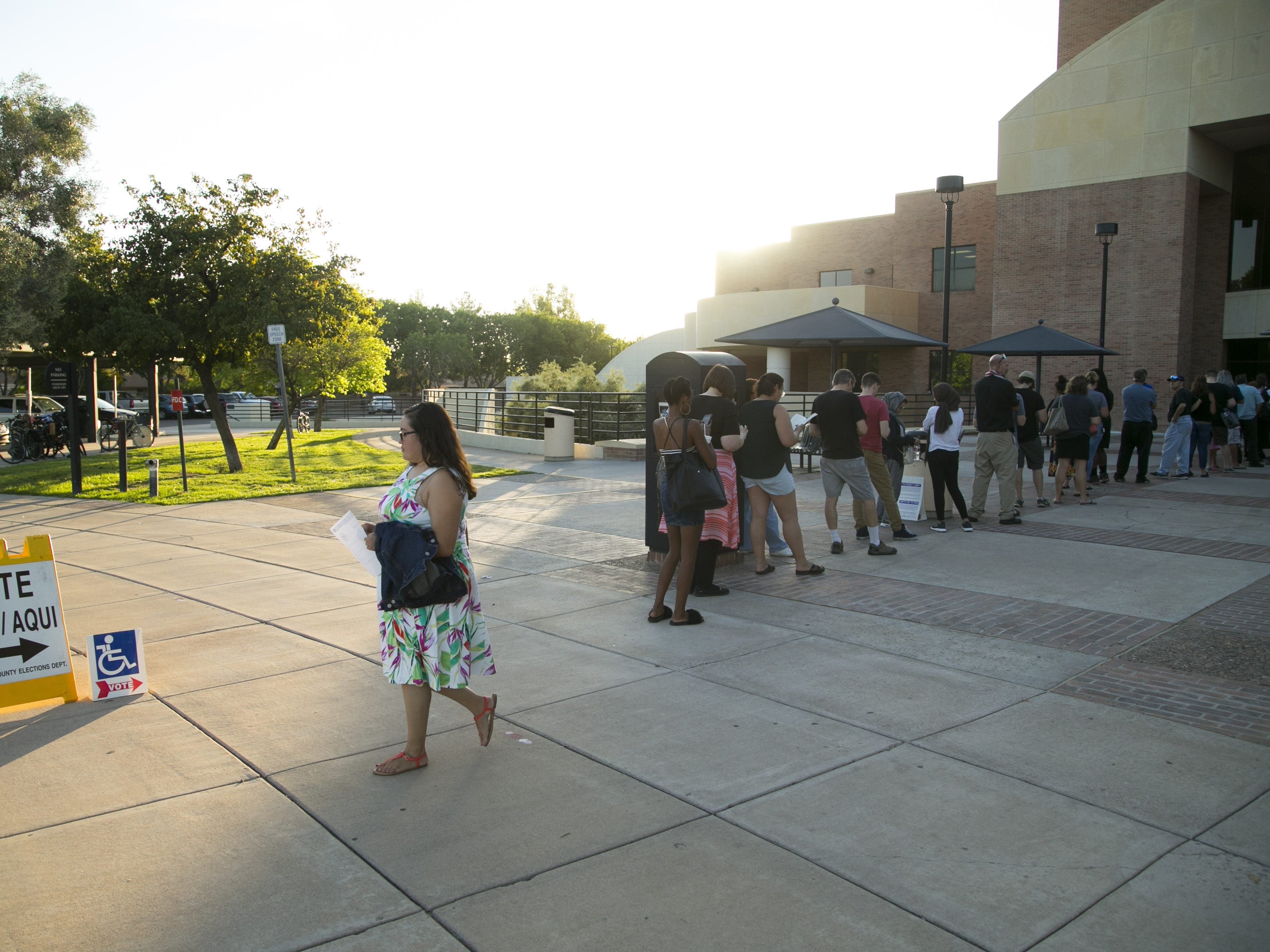 People wait in line to vote in the primary, at the polling place at the Tempe Public Library on Tuesday evening, Aug. 28, 2018. People leaving the polling place said they waited in line for an hour.