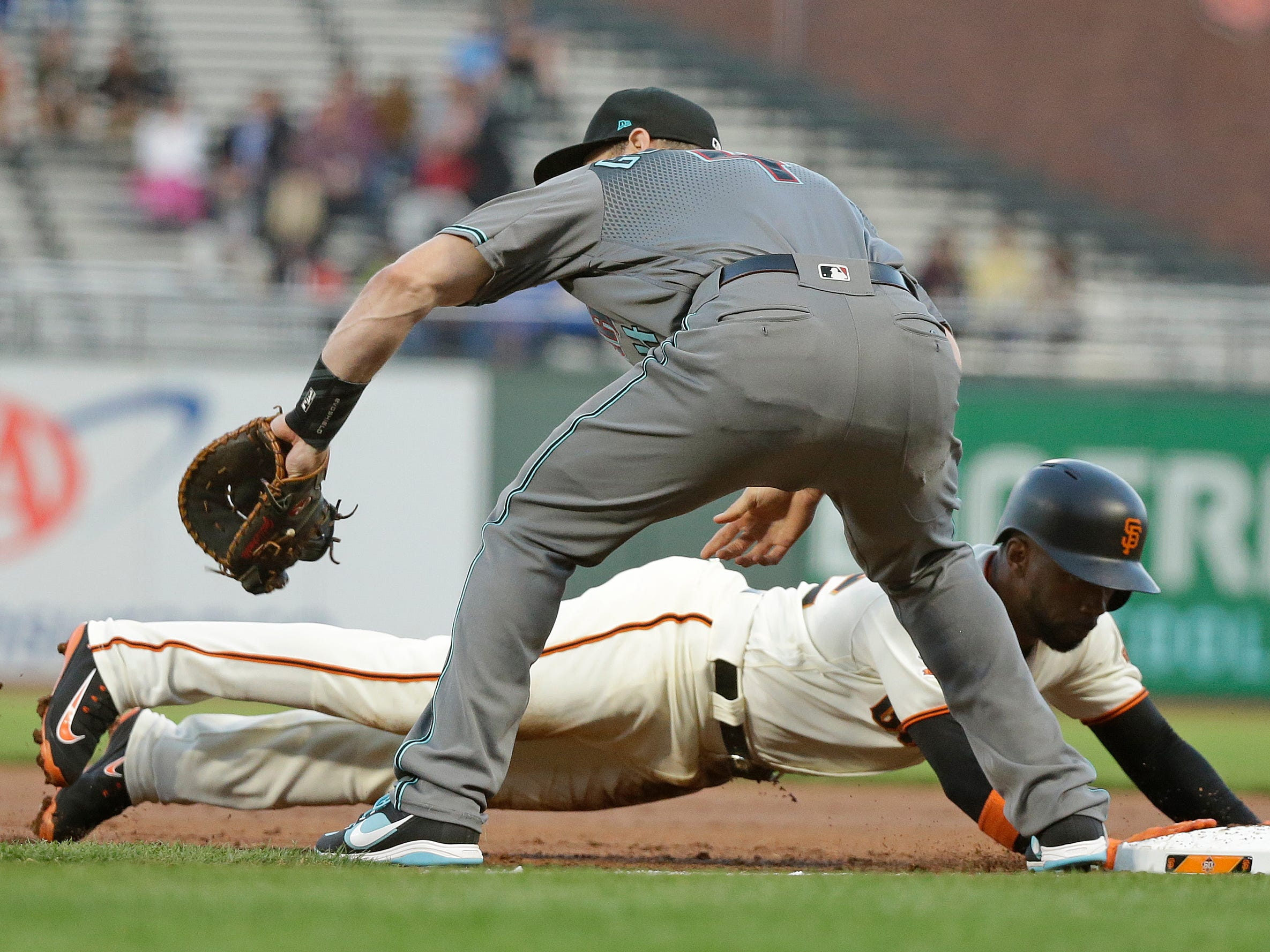 San Francisco Giants' Andrew McCutchen dives safely back to first base on a pick-off attempt as Arizona Diamondbacks first baseman Paul Goldschmidt waits for the throw in the first inning of a baseball game, Tuesday, Aug. 28, 2018, in San Francisco.