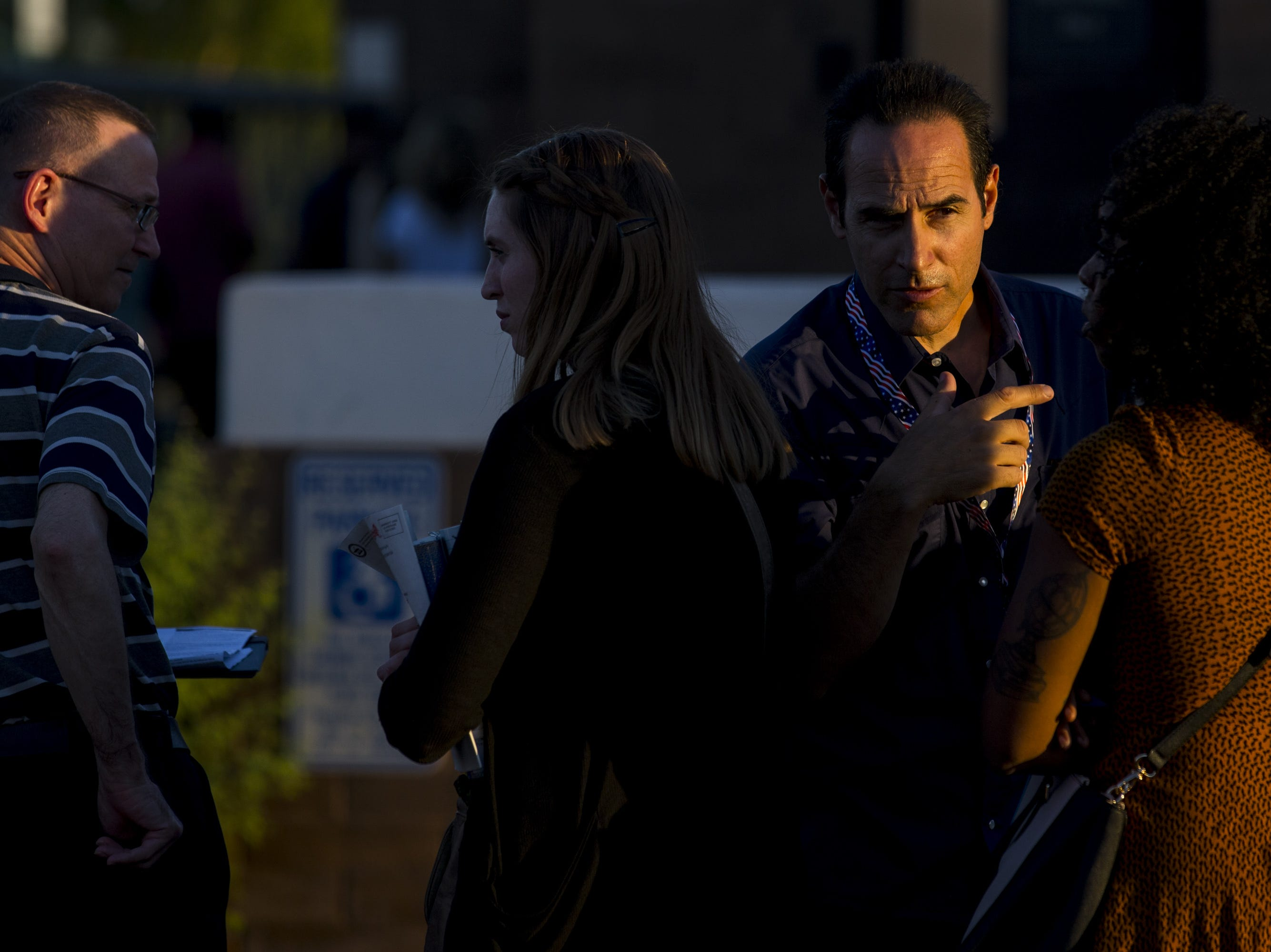 Tristan, a Maricopa County Elections worker, talks to people waiting in line to vote on Tuesday, Aug. 28, 2018, at the Phoenix Public Library Century Branch in Phoenix.