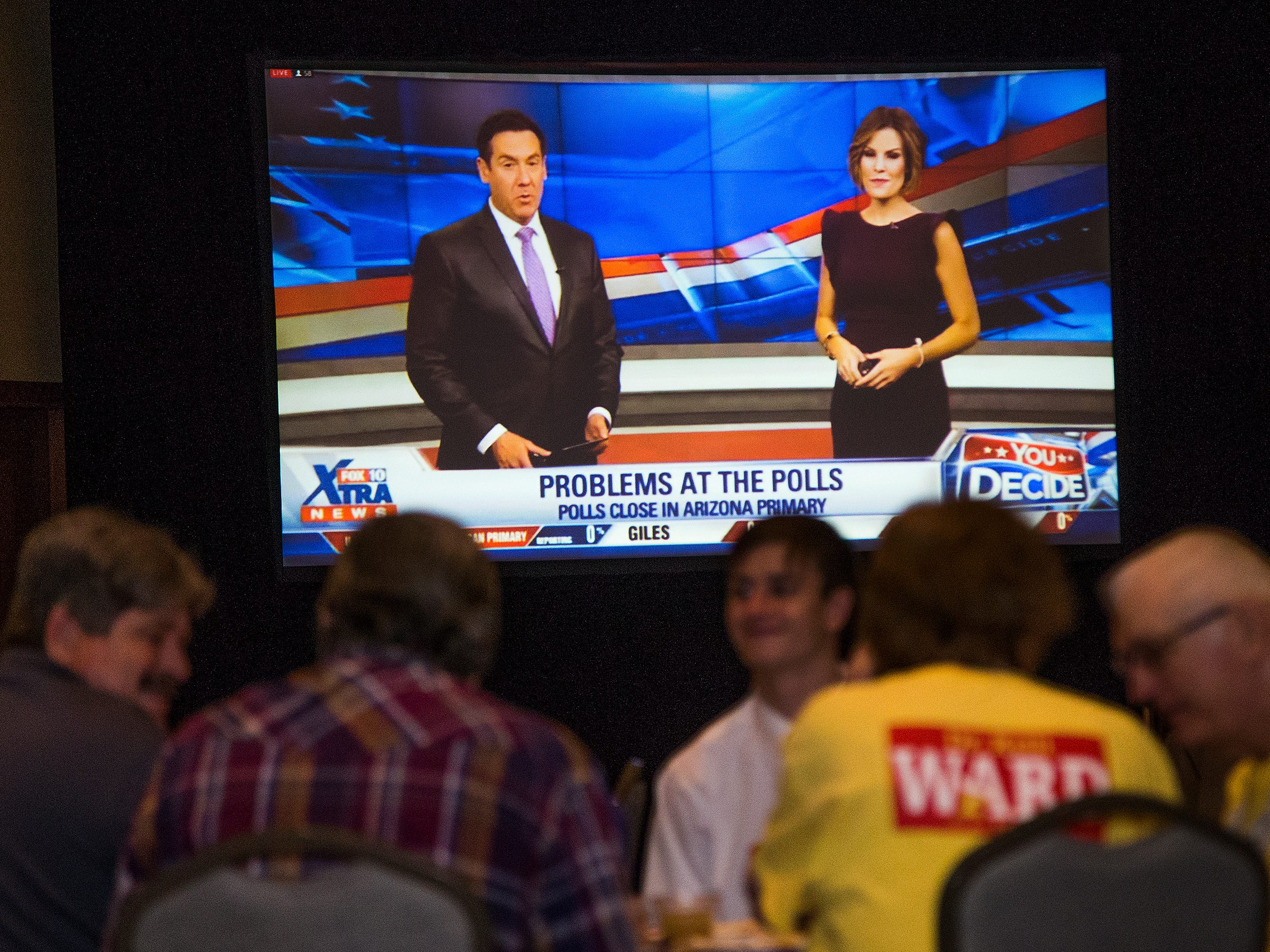 Supporters of Kelli Ward wait for her appearance at a primary election night party at Embassy Suites Scottsdale as reports of problems at the polls appear on a large TV screen on Aug. 28, 2018.