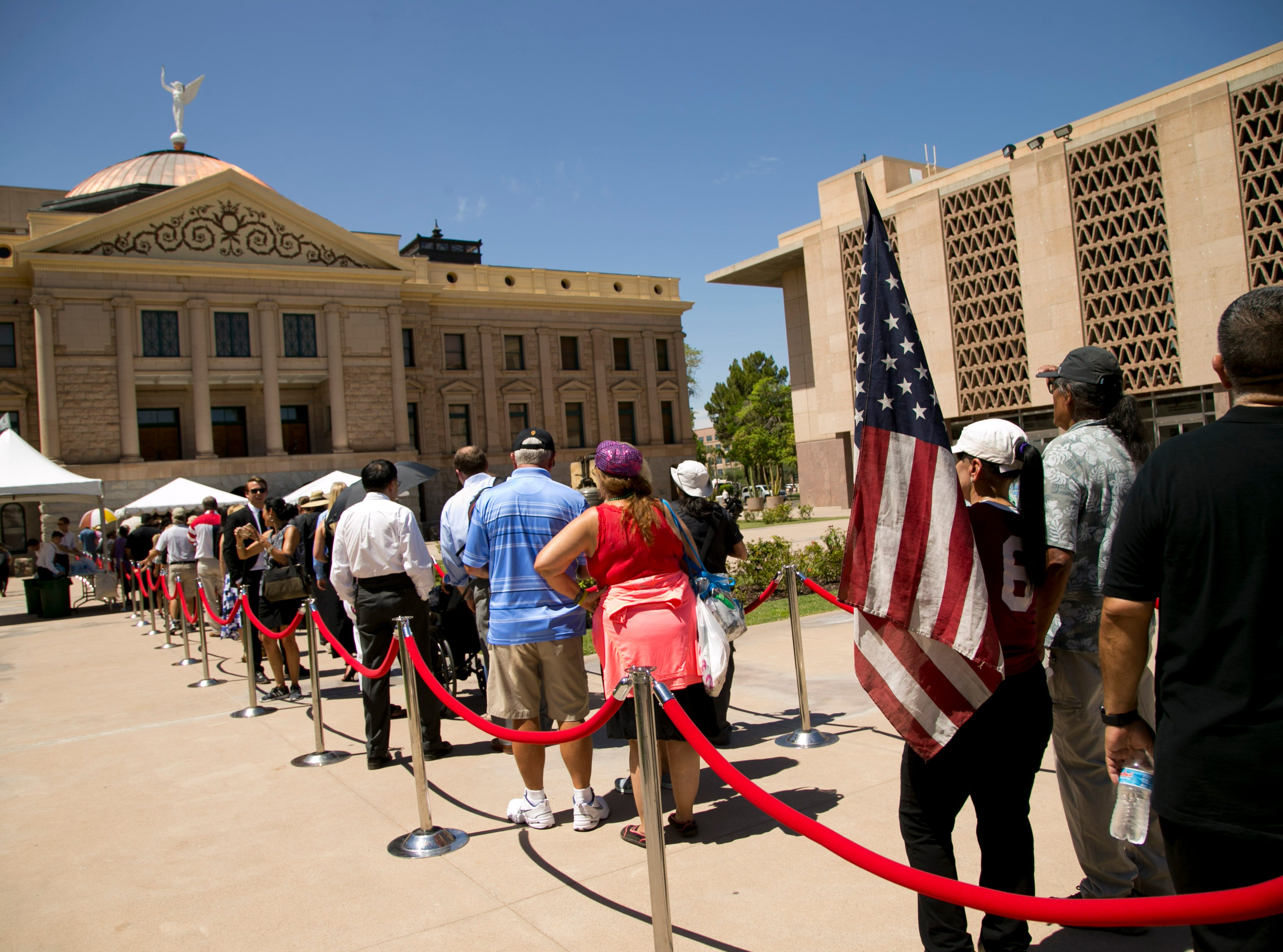 People wait in line to enter the Arizona state capitol during a public viewing as Senator John McCain lies in state in the state capitol in Phoenix on Wednesday, August 29, 2018.