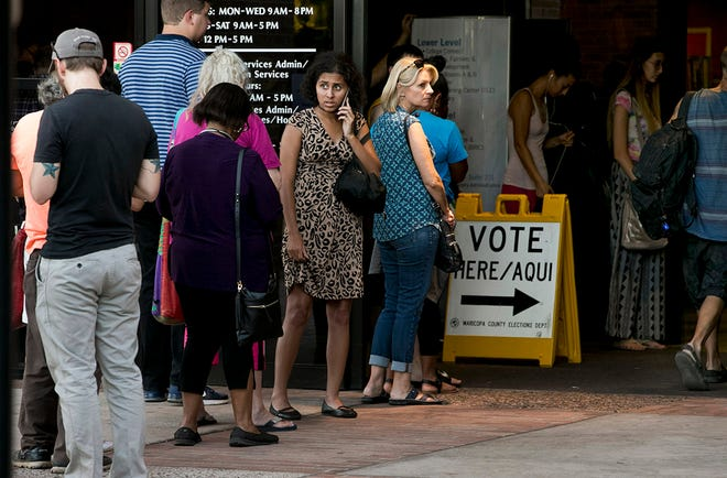 People wait in line to vote for the primary, at the polling place at the Tempe Public Library on Tuesday evening, August 28, 2018. People leave the polling place said they waited in line for an hour.