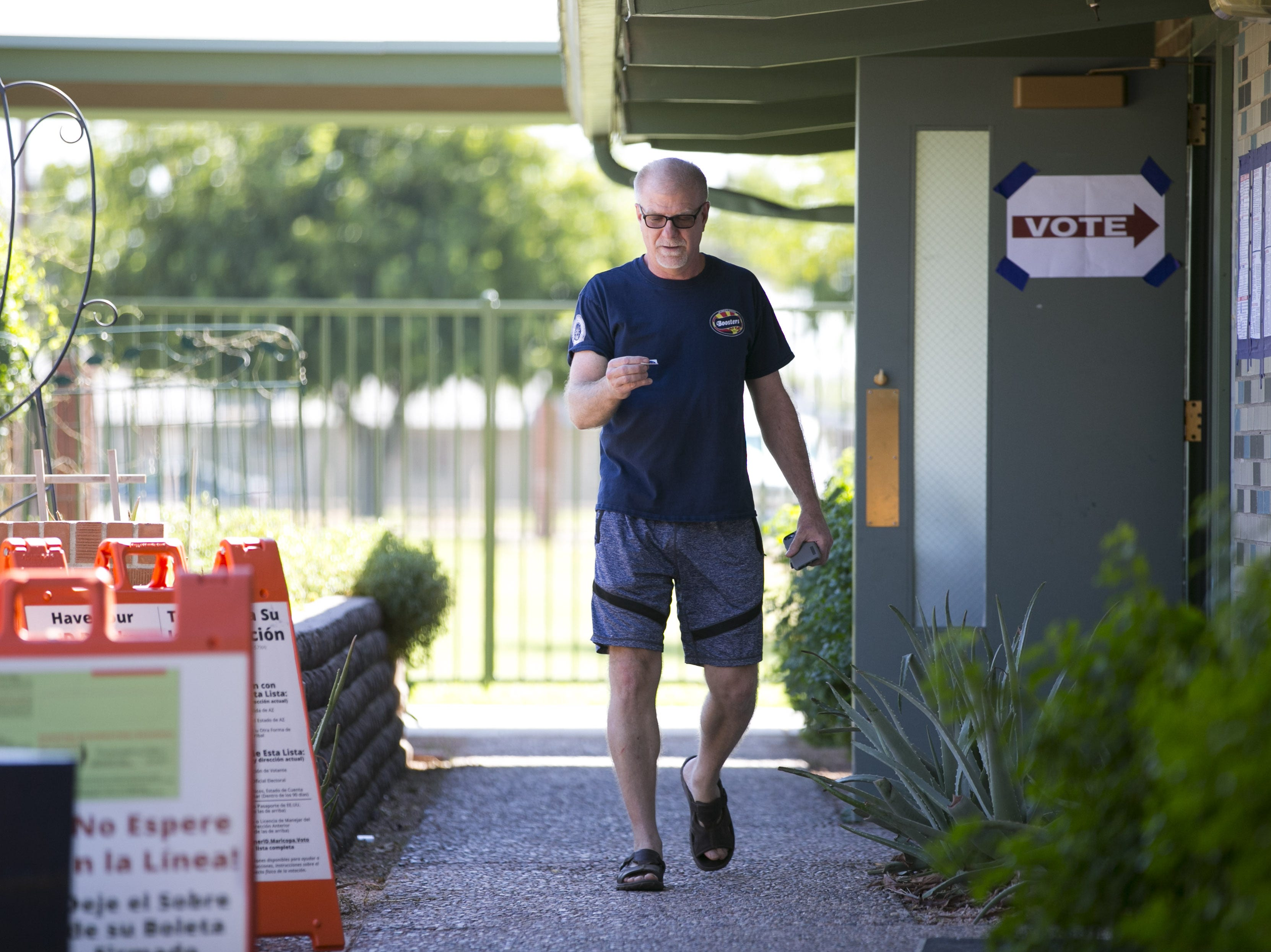 "Roger Baker of Scottsdale looks at his ""I Voted"" sticker after voting in the primary at the polling place at the Paiute Neighborhood Center in Scottsdale on Aug. 28, 2018."