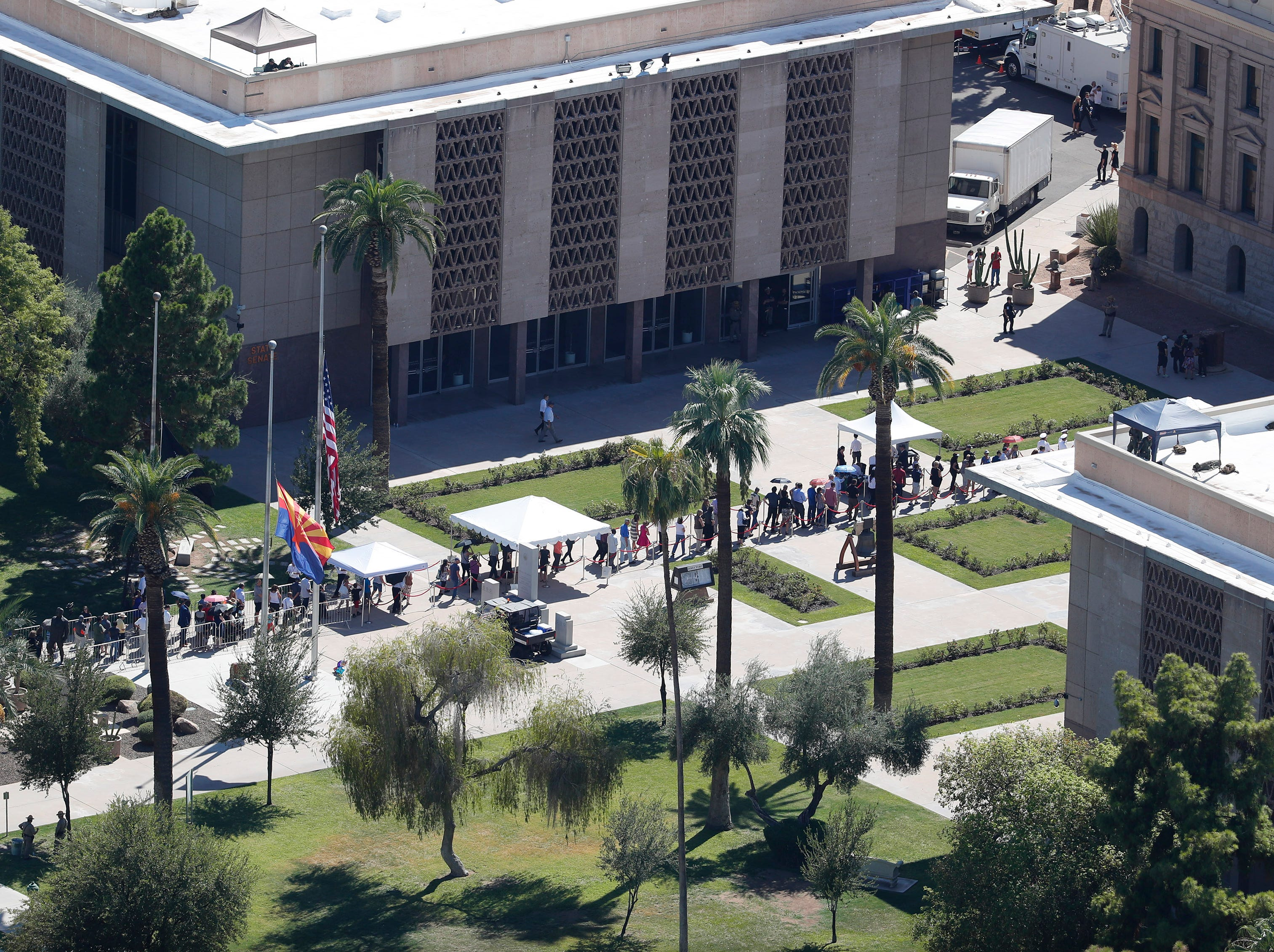 People line up outside the Arizona state Capitol, where Sen. John McCain lies in state in Phoenix Aug. 29, 2018. The six-term Arizona senator died Saturday after a 13-month battle with brain cancer.